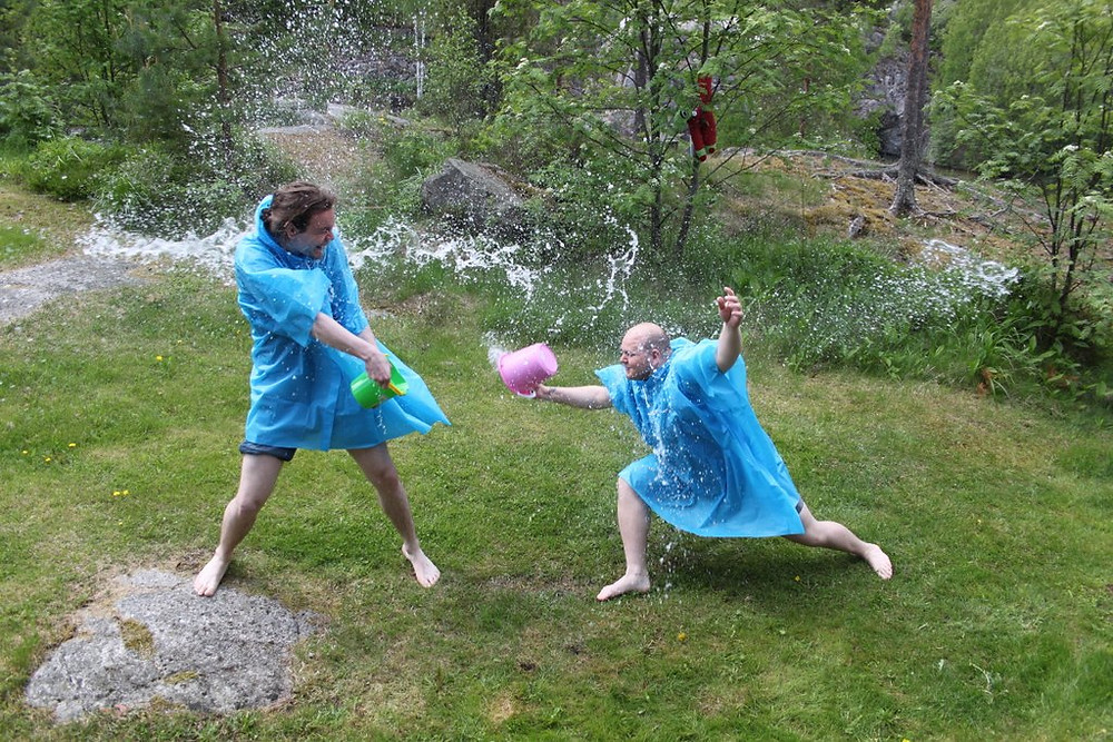 Kaksi HUMAKOlaiset heittävät ämpäreillä toistensa päälle vettä.