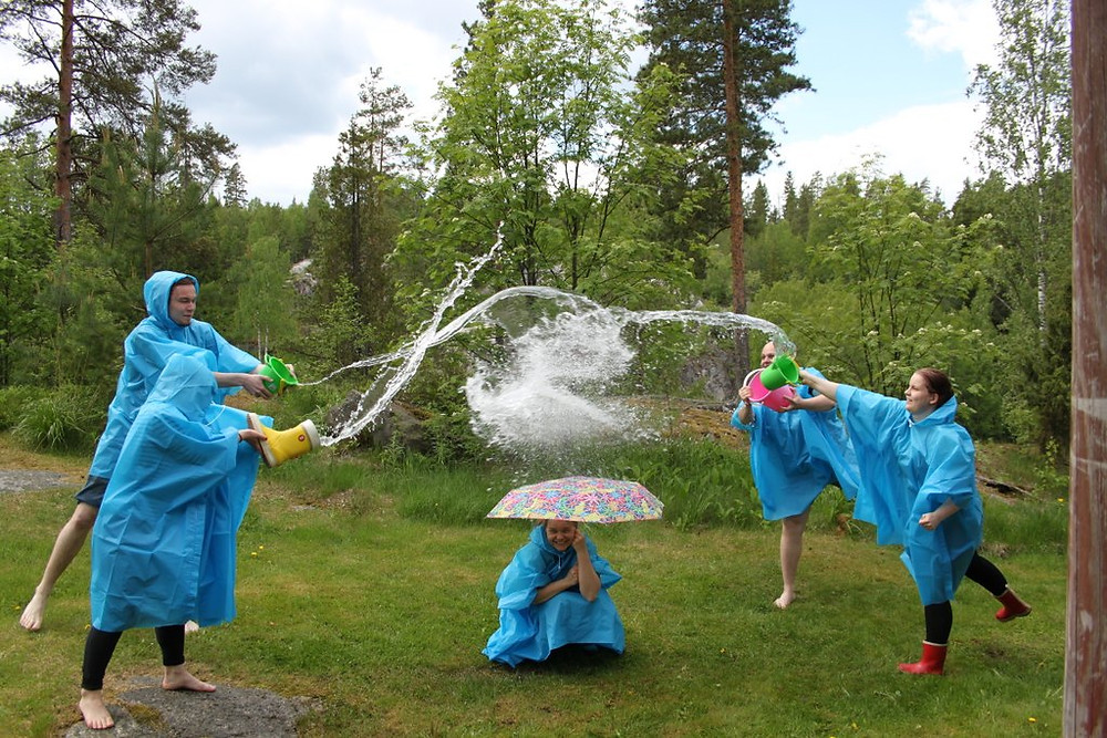 4 students throw water on top of one student under an umbrella.
