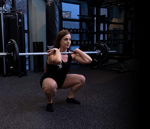 Beth Lavis a Personal Trainer in London doing a front squat with a barbell in the gym.