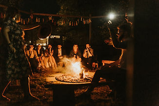People gather around the outdoor fire, on benches with decorations