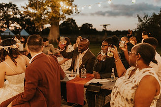 A bride and groom, with guests, raising drinks in glasses as a celebration toast, outdoors at night