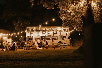 A bride & group of guests outdoors, at night, in front of a retro double decker bus with lights