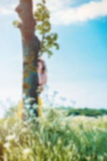 Fotoshooting auf einer Wiese, nahe Lübeck, Mädchen hinter Baum