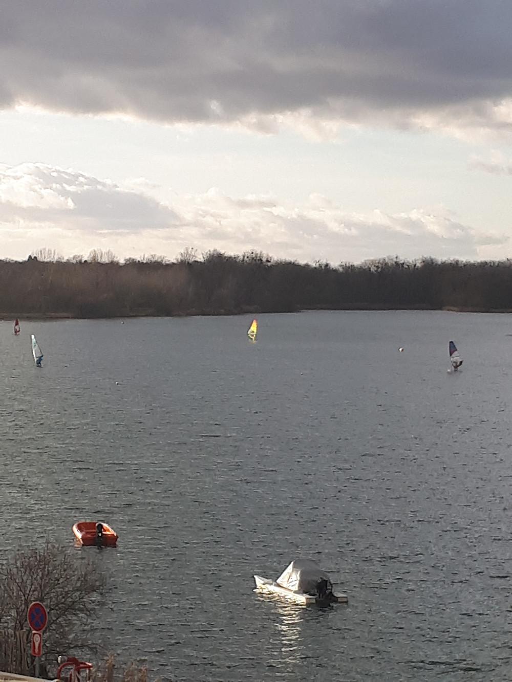 Photographie du lac de Vaires-sur-Marne sur laquelle des bateaux sont attachés et des planches à voiles naviguent au vent.