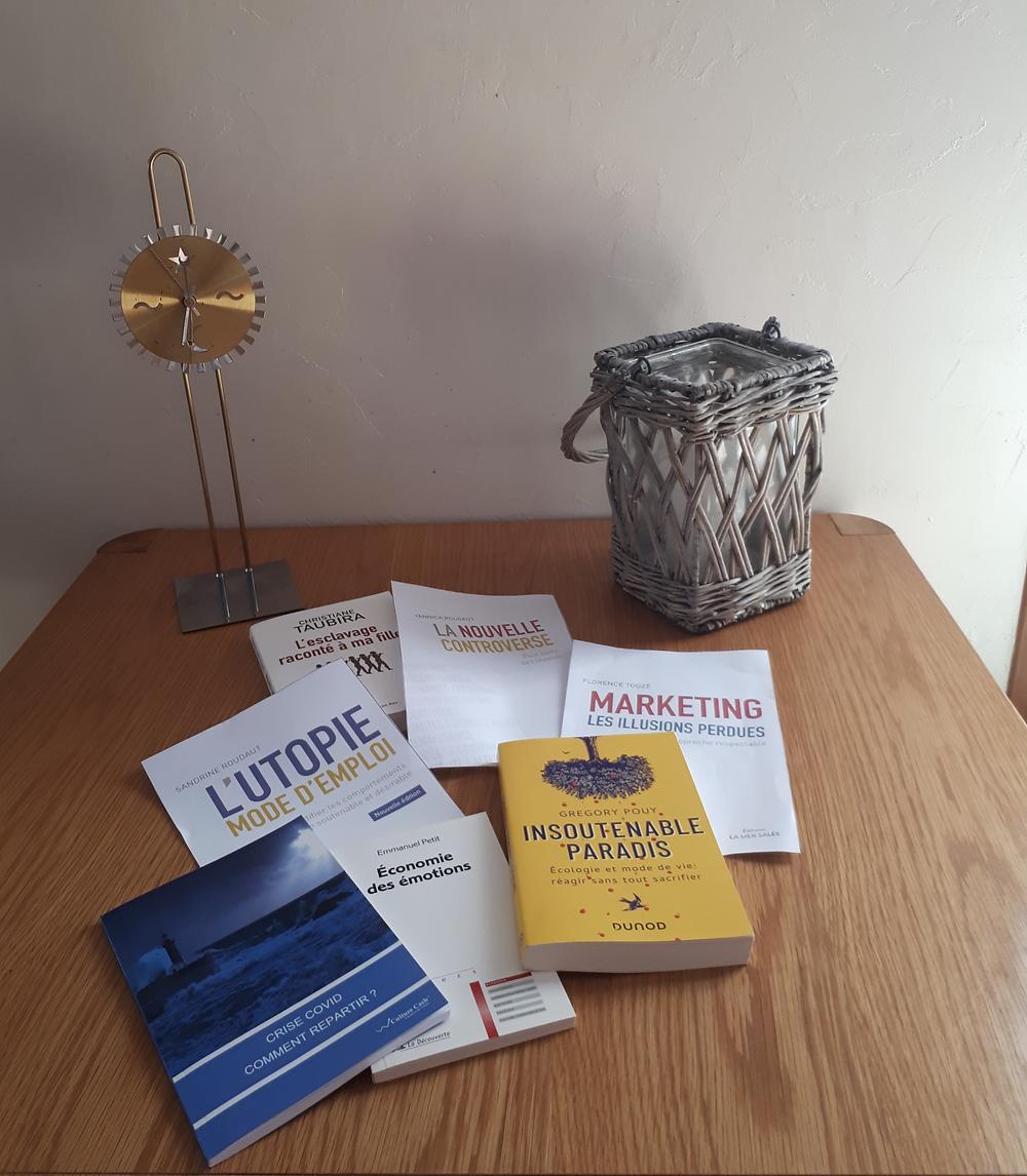 livres posés sur une table avec une horloge et une bougie.
