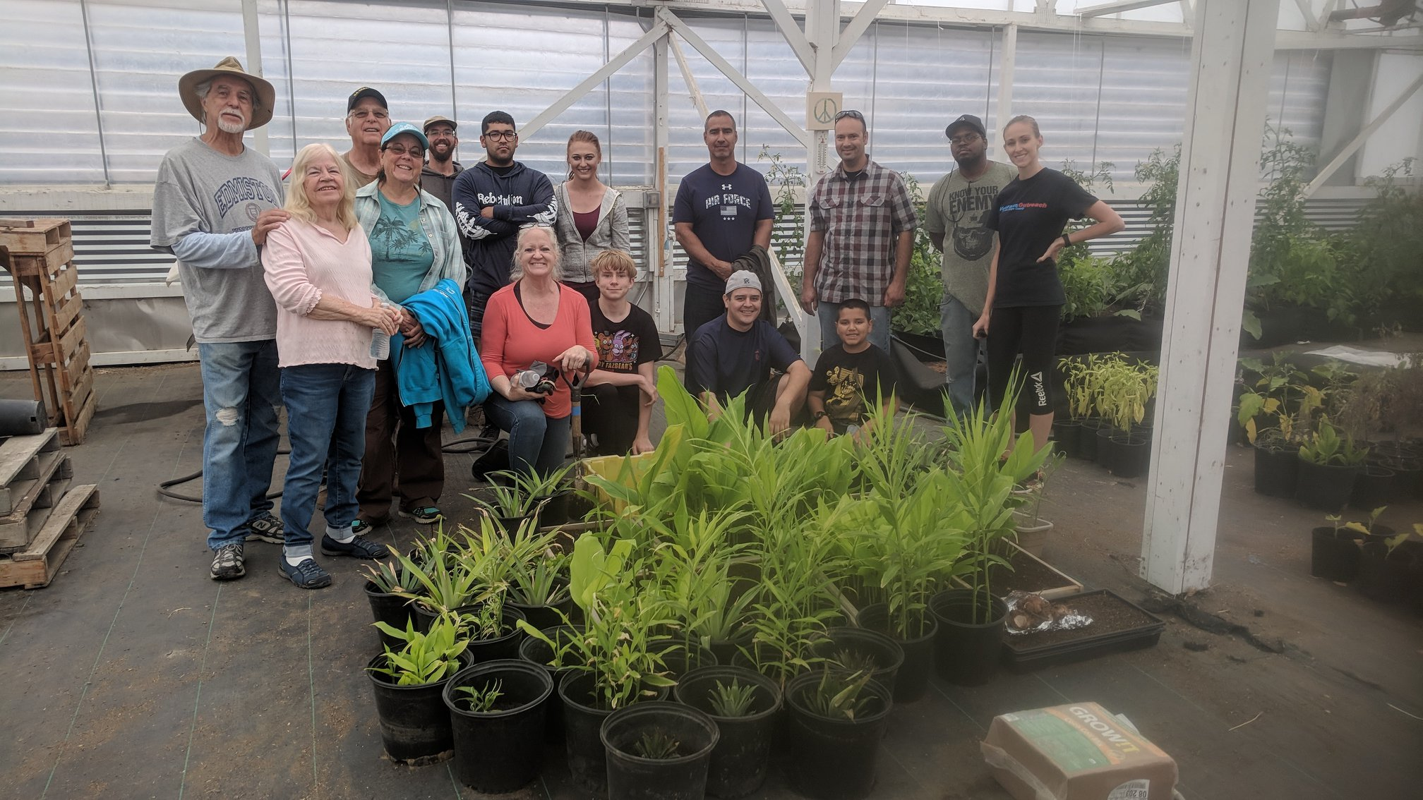 Farm day for veterans, group posing in the greenhouse behind sprouting turmeric and ginger.
