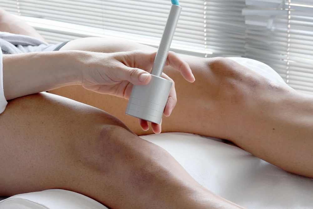 Individual receiving cold laser therapy on the side of their knee cap.