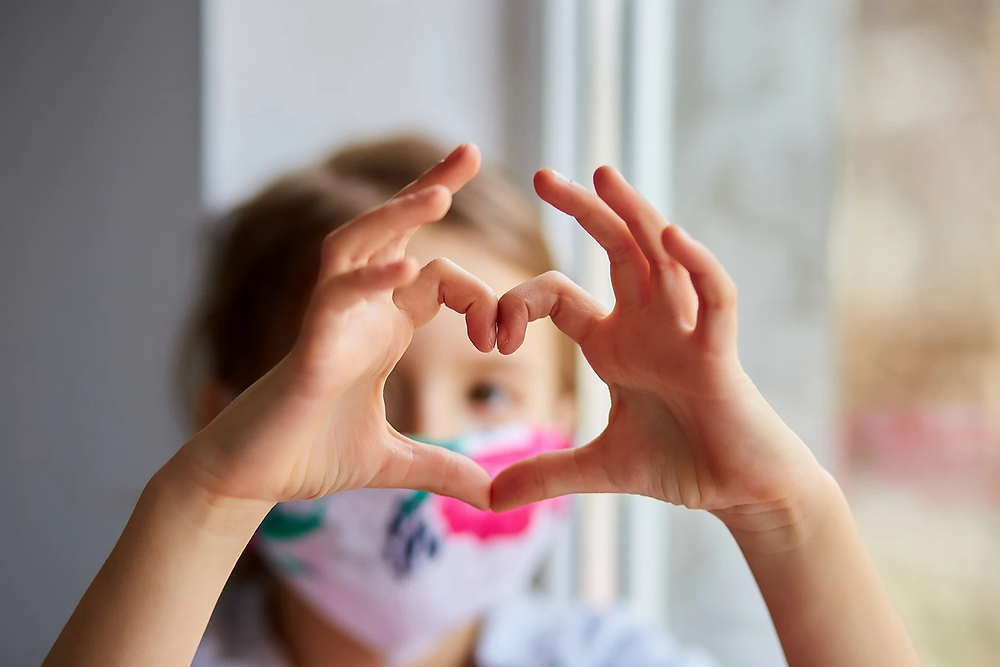 Child making a heart with their fingers.