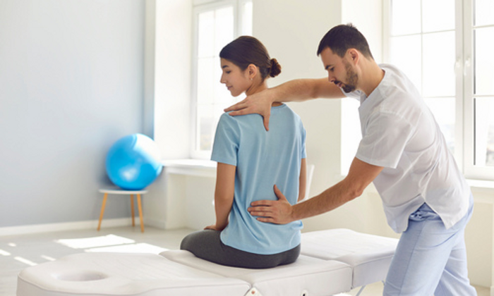 Chiropractor performing a lower back adjustment.