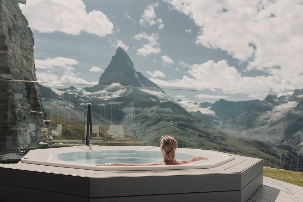 Woman in a hot tub looking at a mountain view for heat chiropractic therapy