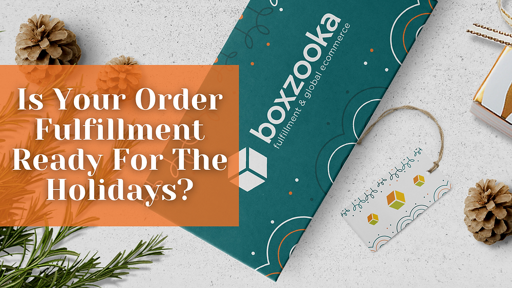Boxzooka Fulfillment & Global E-commerce Order Fulfillment Holiday Envelope On A Table With Two Pinecones.