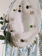 """10"""" metal hoop wrapped with fabric, knotted web, faux eucalyptus, ribbons, fabric, yarns, beads and feathers."""