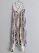 """8"""" metal hoop wrapped with ribbon, knotted web with yarns, ribbons, beads and feathers."""