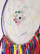 """10"""" metal hoop wrapped with yarn, knotted web, beads, ribbons, yarns and feathers."""