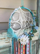 """8"""" metal hoop wrapped in yarn with ribbons, yarns, faux flowers and feathers"""