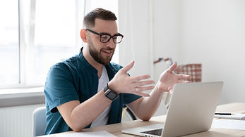 Millennial Caucasian male worker in glasses have video call on laptop in office, smiling y