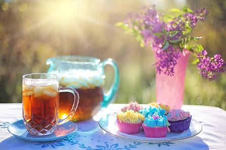 table d'été avec thé glacé, cupcake et fleurs