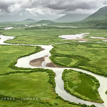 Glacial River Flows Through Green Valley