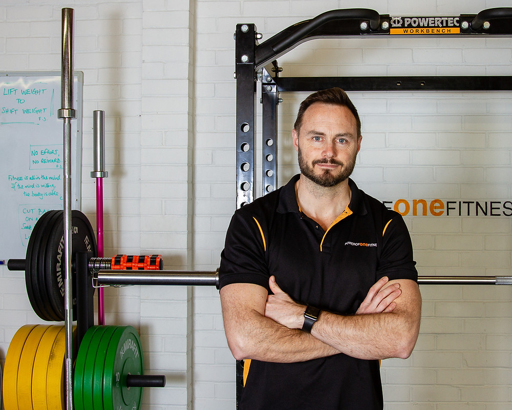 Business brand photography: Personal trainer in a studio gym with large and colourful weightlifting weights behind him. In Waltham St Lawrence