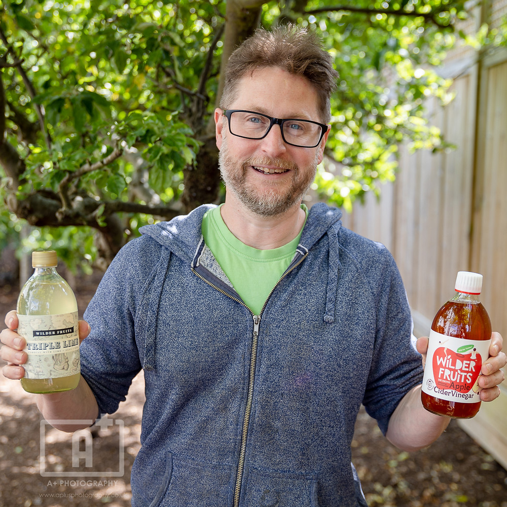 A smiling man outside, holding two bottles of cordial and vinegar.
