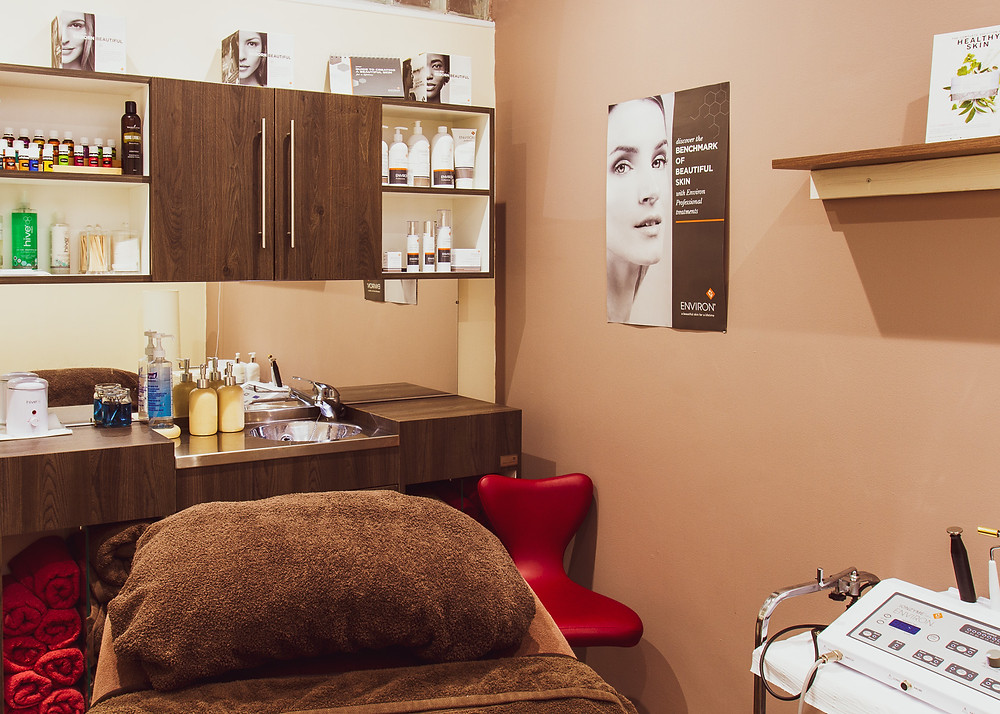 Business photography | photo of massage table with skin care products and essential oils on shelves