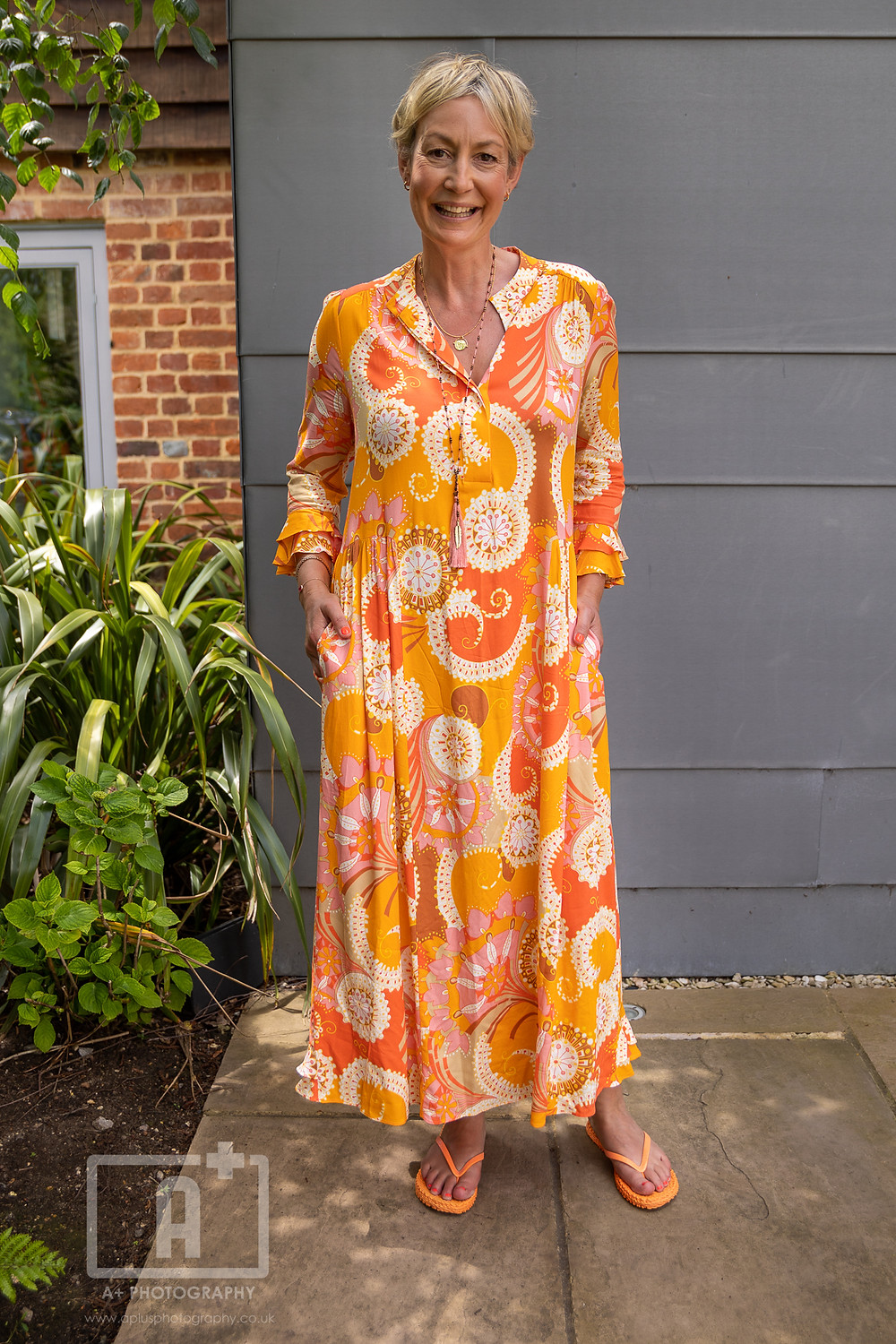 A woman standing in a long flowery orangey yellow dress in front of a grey wall.