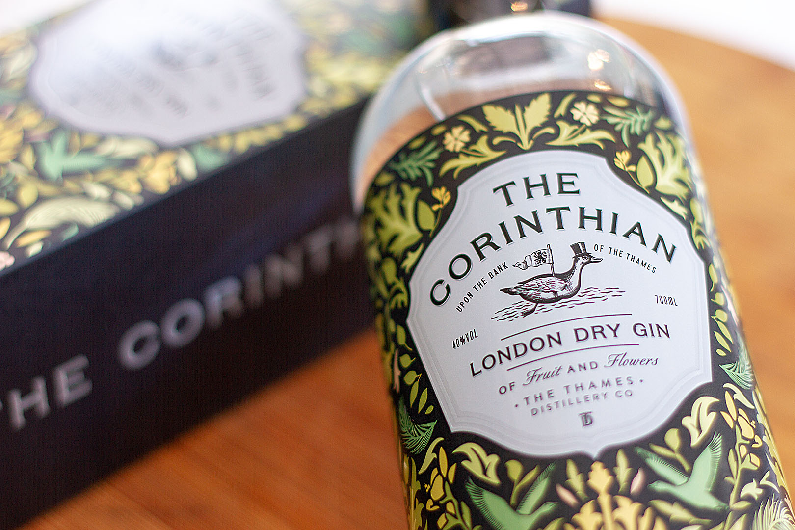 Product photography: A gin bottle resting partially on its box with the labels clearly legible on a