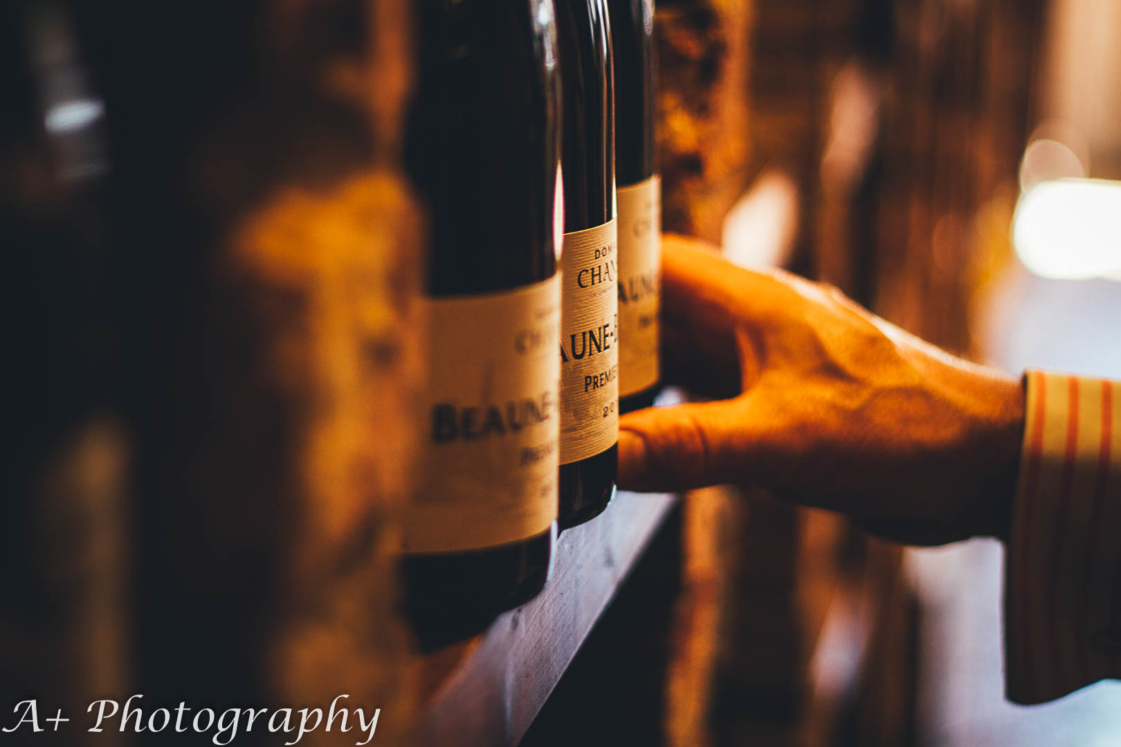 Moody product photography: A hand reaching for a wine bottle on a shelf
