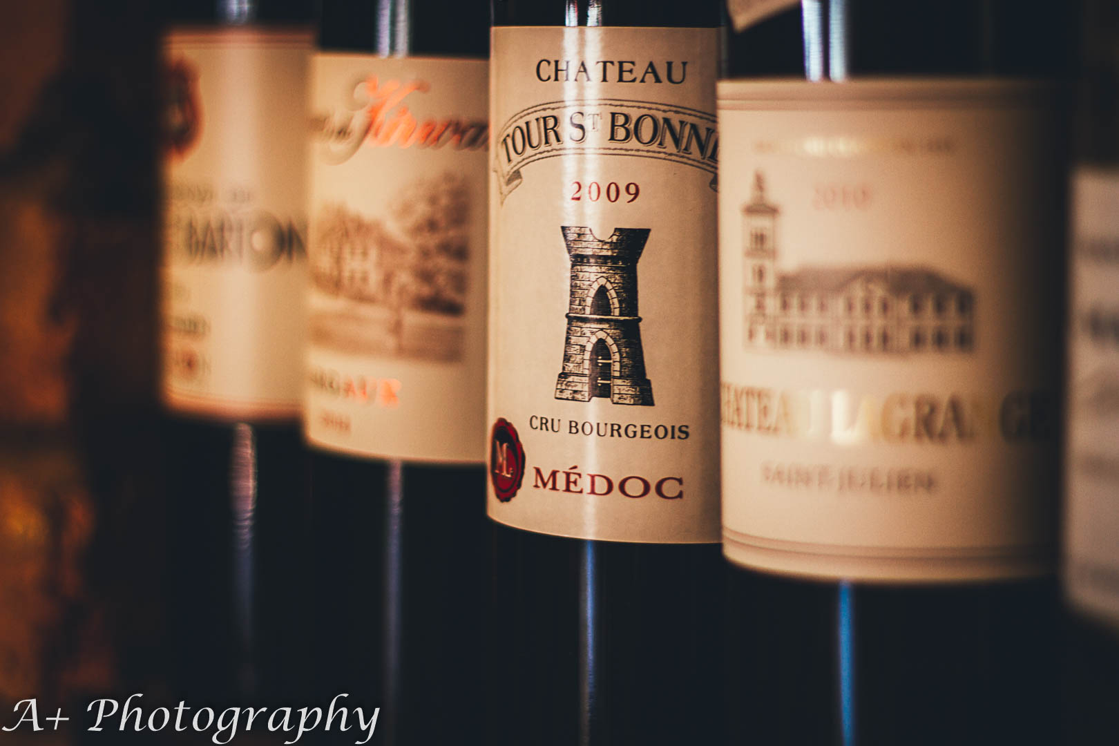Moody product photography: Several red wine bottles together on a shelf