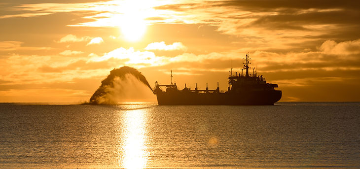 Vessel engaged in dredging at sunset tim