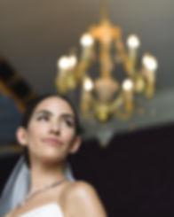 bride getting ready for wedding beneath chandelier