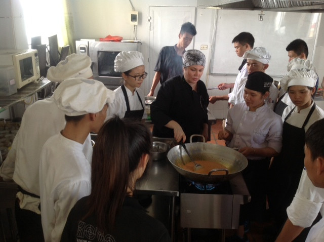 Vicky Acosta, Colombian Celebrity Chef, and Charge d'Affaires ep Alban Carlos Alfonso Franco, speaks with 30 KOTO cooking class trainees.