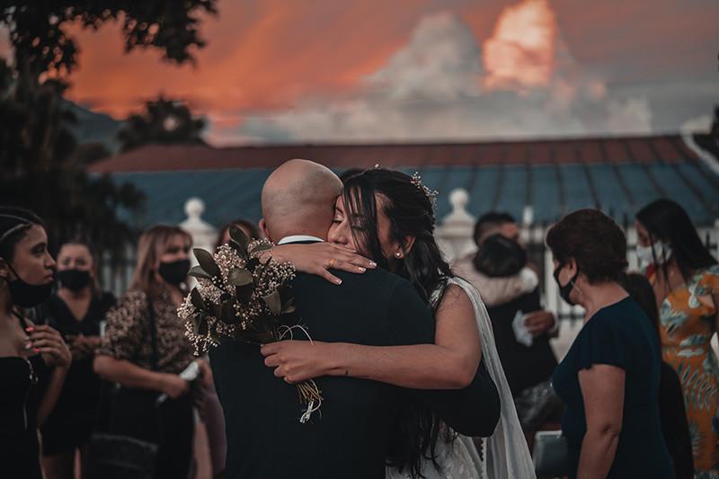 noivos se abraçam em festa de casamento com máscara