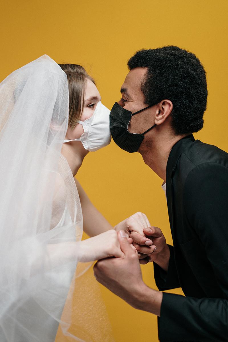 noivos se beijam de máscara na pandemia