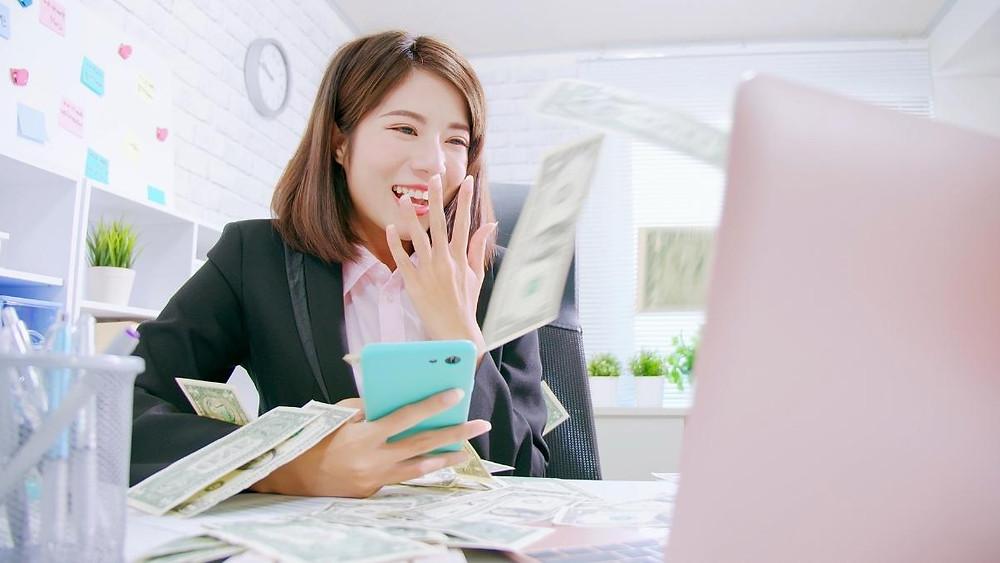 mulher feliz, sorridente, recebendo pagamentos pela internet em casa