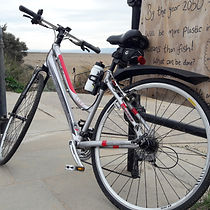bicycle leaning against a post and message board