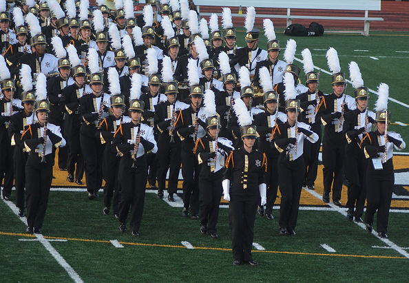 Marching Mustang band members in full uniform ready to perform.
