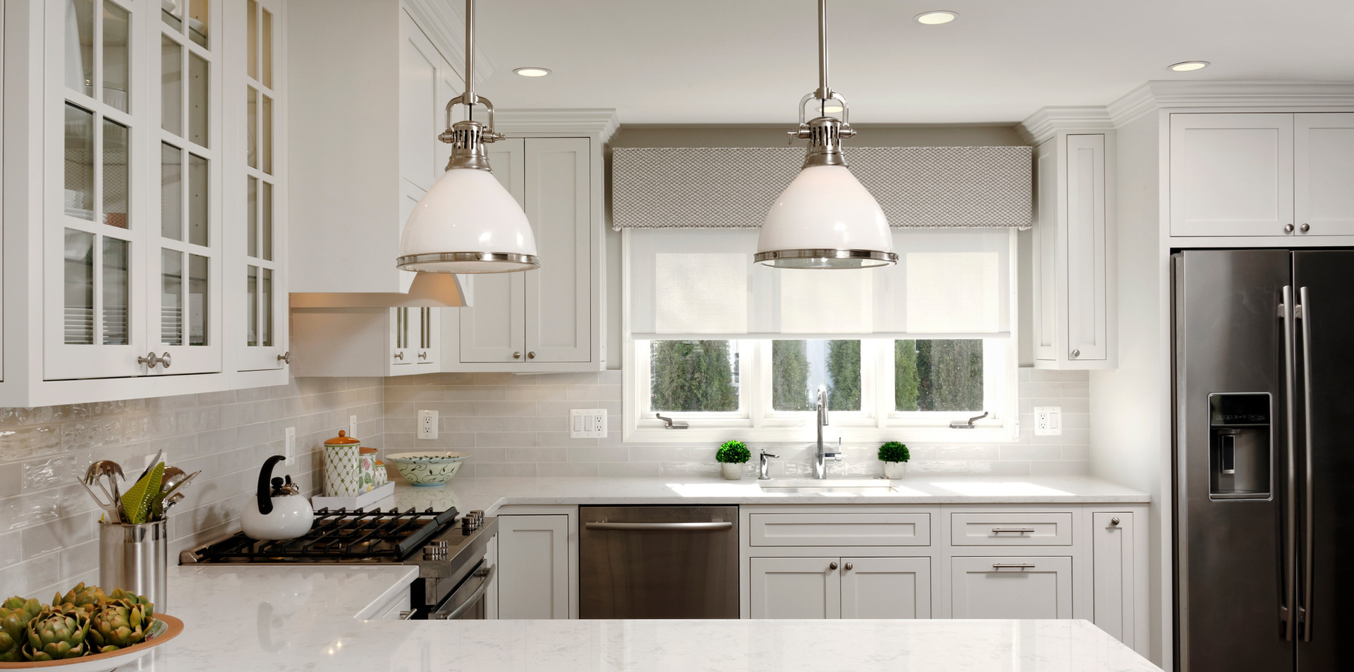Modern Kitchen with Glass Cabinetry and Pendant Lights
