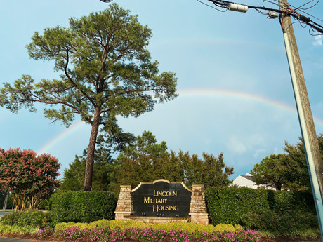 """""""I was just taking a photo of the rainbow today from my car and the Norfolk Lincoln Military housing sign happened to be perfectly under the rainbow. - Arielle Baxley, LMH Resident"""""""