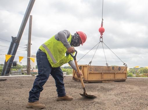 Roofing crew shoveling gravel