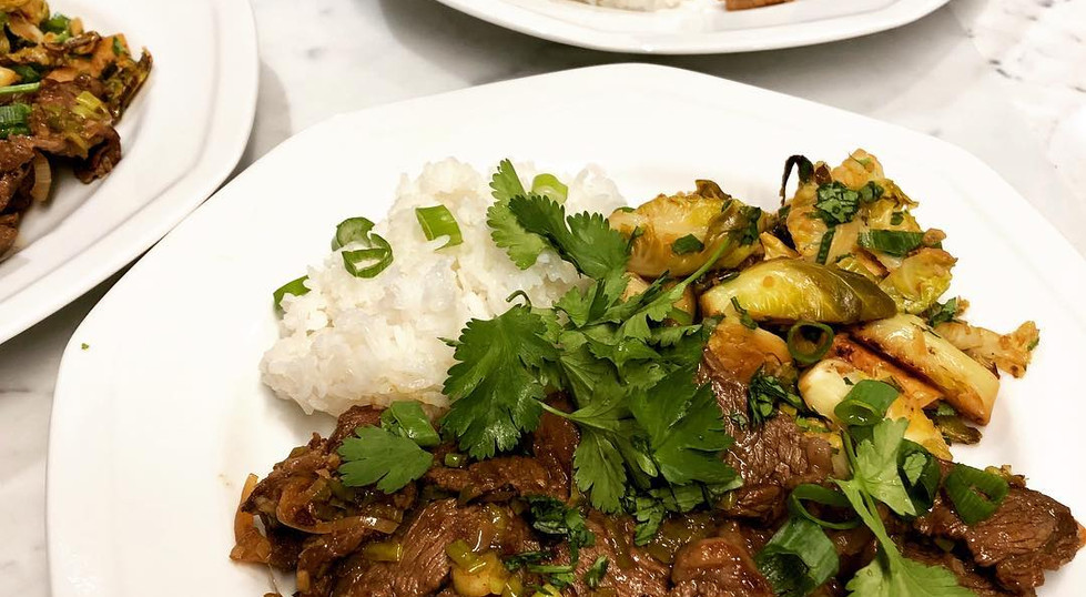 Vietnamese stir-fried beef and caramelized Brussels Sprouts with scallions and cilantro over stove-top jasmine rice
