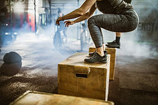woman in grey leggins jumping onto a wooden box