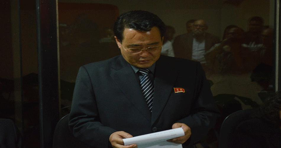 O novo embaixador da RPDC, Kim Chol Hak, faz uma saudação no ato
