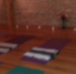 Yoga mats, candles and fresh flowere set up in a Yoga studio.