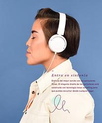 Vista lateral de una mujer con auriculares, escuchando música.
