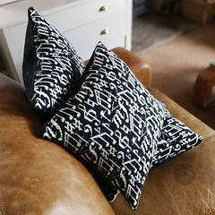 2 knitted cushions patterned with music notes on a sofa