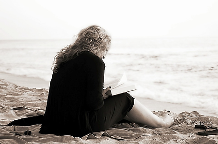 Woman relaxing and reading by the beach