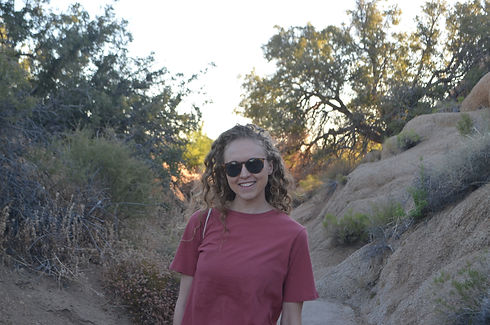Picture of Liv smiling with sunglasses in the desert.