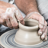 Closeup of an adult throwing a pot on the wheel.