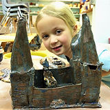 Girl smiles as she stands behind glazed castle built out of clay